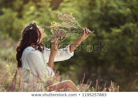 Attractive woman smelling wild flowers Stock photo © konradbak