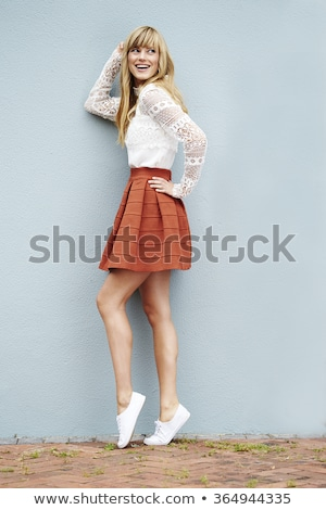 Smiling woman posing with one hand on hip Stock photo © stockyimages