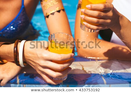 Girlfriends clinking glasses with cocktails at the poolside bar Stock photo © Yatsenko