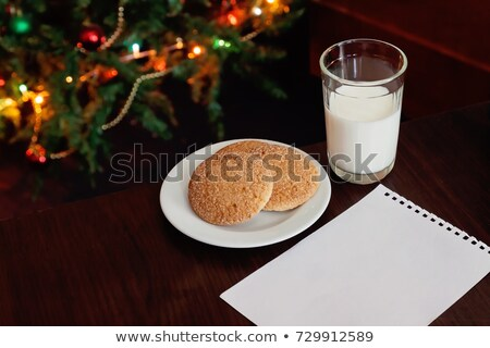 christmas cookies and milk with note for santa in front of light stock photo © tanach