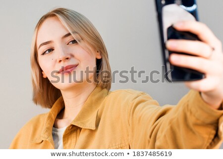 young pretty blond woman with smartphone posing smiling making stock photo © iordani