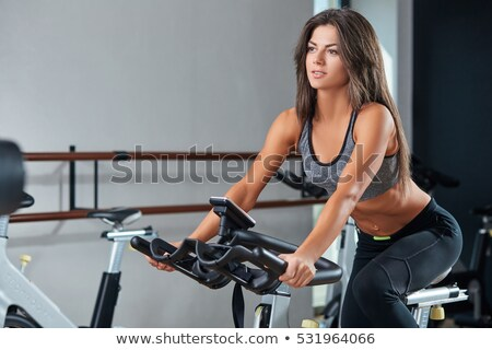 exhausted young woman on exercise bike stock photo © is2