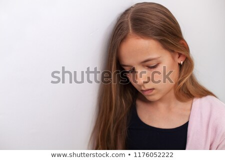 Sad teenager girl standing by the white wall with downcast eyes Stock photo © ilona75