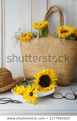 closeup of sunflowers in straw purse on table stock photo © sandralise
