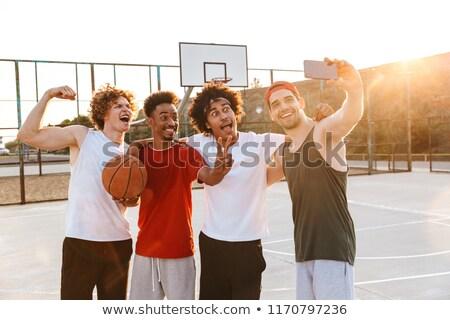 Erős több nemzetiségű férfiak mosolyog elvesz okostelefon Stock fotó © deandrobot