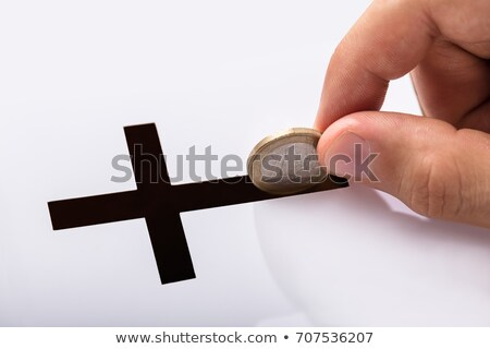 person inserting coin in crucifix slot stock photo © andreypopov