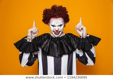 Stockfoto: Scary Angry Clown Pointing Up At Copy Space