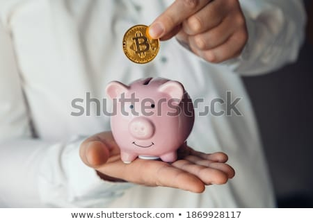 businessman inserting a bitcoin in a piggy bank Stock photo © nito