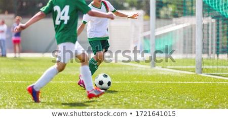 Boy kicking soccer ball. Close up action of boys soccer teams, aged 8-10, playing a football match Stock photo © matimix