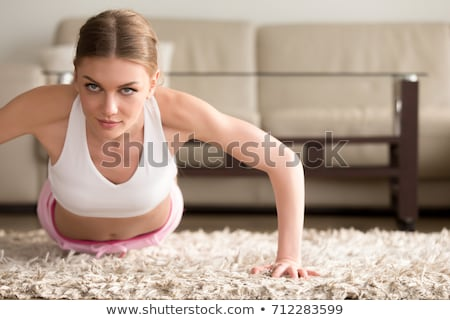 young woman doing plank exercise working on abdominal muscles an stock photo © boggy