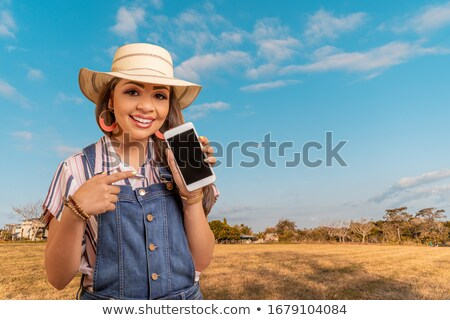 pretty young lady outdoors in the field using mobile phone wearing hat stock photo © deandrobot