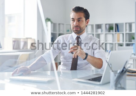Busy young elegant trader having glass of water in front of computer screen Stock photo © pressmaster