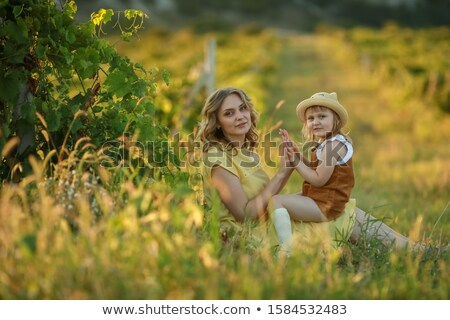 A woman sits in a natural field near a green Bush and plays with a child Stock photo © ElenaBatkova