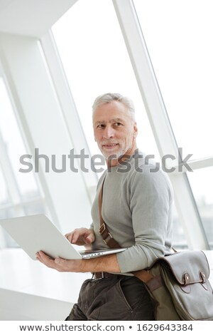 Photo of pleased gray-haired man holding and using laptop Stock photo © deandrobot