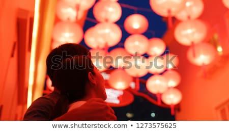Woman celebrate Chinese New Year look at Chinese red lanterns. Chinese lanterns are reflected in gla Stock photo © galitskaya