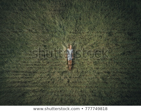 Young woman lying down in the middle of a field and relaxing, drone photo Stock photo © galitskaya