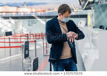 Coronavirus outbreak. Man passenger checks time, poses against blurred airport background, wears med Stock photo © vkstudio