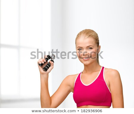 Woman squeezing hand grippers Stock photo © photography33
