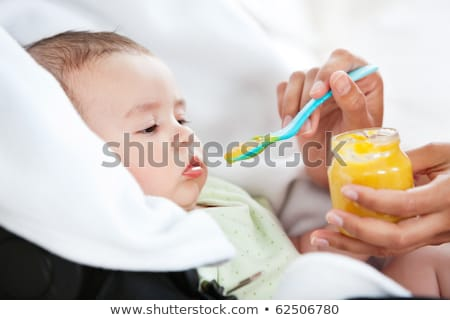 Close-up of a mother giving food to her cute baby at home Stock photo © wavebreak_media