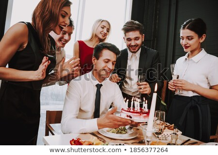Woman putting candles in cake smiling Stock photo © monkey_business