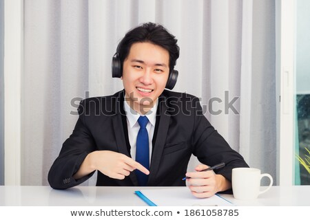 Stock photo: business student at a business suit sitting at his desk and show