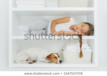 Shot of sleeping small girl lies on white shelf, has pleasant dreams, dressed in casual clothes, has Stock photo © vkstudio