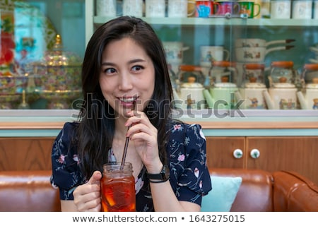 Closeup portrait image of a beautiful woman drinking ice tea with feeling happy in green nature and  Stock photo © galitskaya