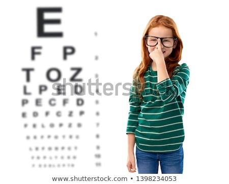 red haired girl in glasses over eye test chart Stock photo © dolgachov