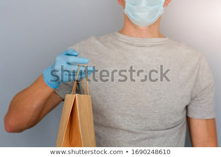 Courier, delivery man in medical latex gloves and mask safely delivers online purchases  during the  Stock photo © Illia