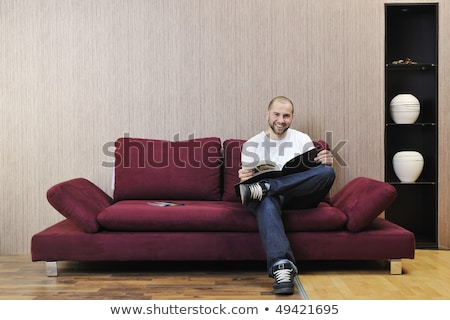 Young Man Sits On Red Leather Sofa Сток-фото © dotshock