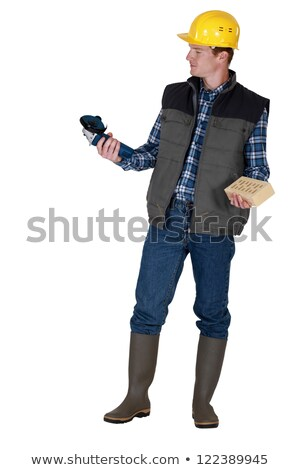 Tradesman holding an angle grinder and a brick Stock photo © photography33