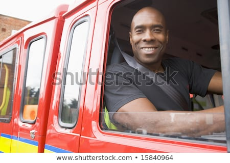 A firefighter sitting in the cab of a fire engine Stock photo © monkey_business