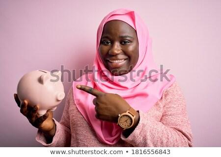 Muslim business woman holding a piggy bank. Stock photo © RAStudio