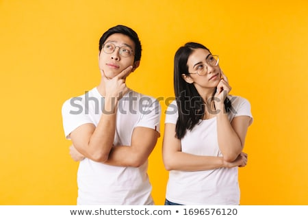 young asian beautiful attractive woman posing isolated indoors pointing stock photo © deandrobot