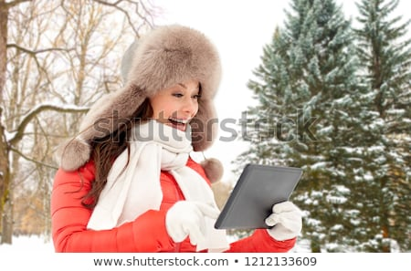 Stockfoto: Woman In Fur Hat With Tablet Pc Over Winter Forest