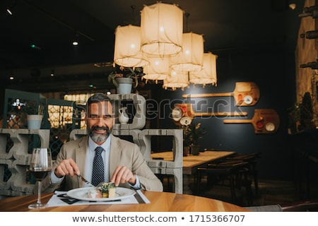 Handsome mature man drinking red wine during lunch Stock photo © boggy