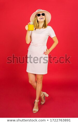 Gorgeous woman holding a glass of orange juice while standing against a white background Stock photo © wavebreak_media