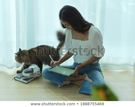 Woman using pad with cat on the lap Stock photo © d13