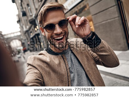 Portrait of a confident young man in eyewear Stock photo © deandrobot