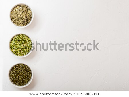 Bowl of mung beans and split peas and pumkin seeds on white ston Stock photo © DenisMArt