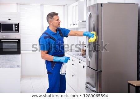 Férfi gondnok takarítás hűtőszekrény szalvéta citromsárga Stock fotó © AndreyPopov