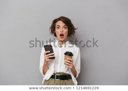 Photo of pleased woman 20s holding takeaway coffee and using mob Stock photo © deandrobot