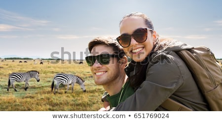 happy woman with backpack over african savannah Stock photo © dolgachov