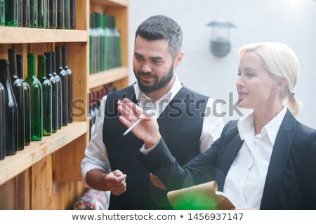 Confident blonde female sommelier and her colleague discussing sorts of wine Stock photo © pressmaster
