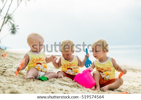 three baby toddler sitting on a tropical beach in thailand and playing with sand toys the yellow sh stock photo © galitskaya