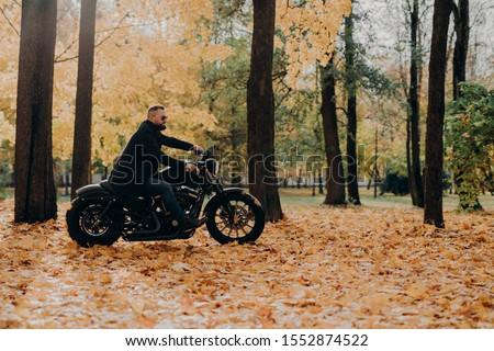 Handsome carefree bearded motorcyclist rides fast motorbike, wears shades, rides bike in park, poses Stock photo © vkstudio