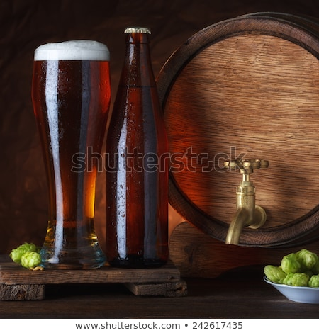 Cold glass of craft beer on old wooden barrel Stock photo © DenisMArt