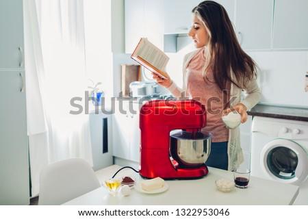 Woman in kitchen reading recipe  Stock photo © studiofi