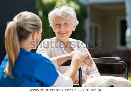 Smiling nurse assisting senior woman sitting in a wheelchair Stock photo © wavebreak_media