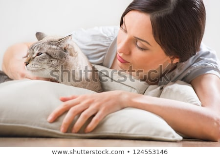 An attractive woman and her cat relaxing on pillows on floor at  stock photo © HASLOO